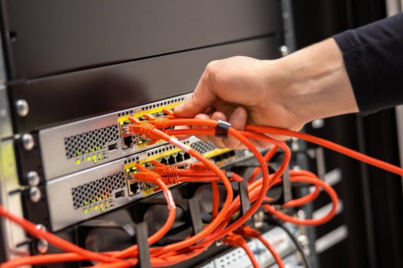 Close-up of Male Technician Plugging Network Cable In Network Router